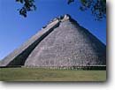 Stock photo. Caption: Pyramid of the Magician Mayan Ruins of the Classic Period Uxmal south of Muna Yucatan,  Mexico -- temple temples ruin pyramids native american tropical destination destinations world central america tourist travel landscape landscapes attraction attractions vacation vacations precolumbian columbian building buildings summer stone blue latin sky skies